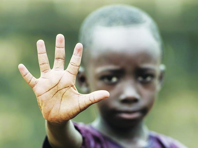 African boy holding his hand up to the camera