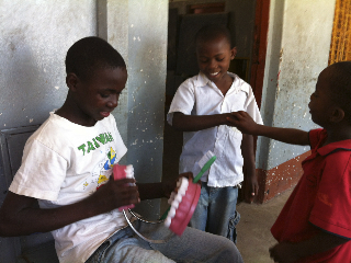 children practicing with giant toothbrush and teeth model